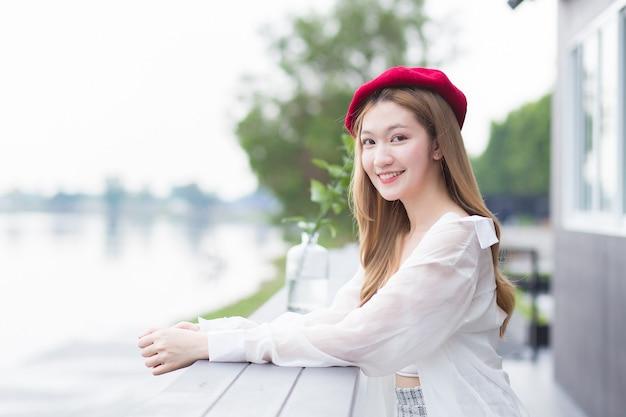 Une belle femme asiatique aux cheveux bronze porte une chemise blanche et un bonnet rouge sourit est assise sur une chaise