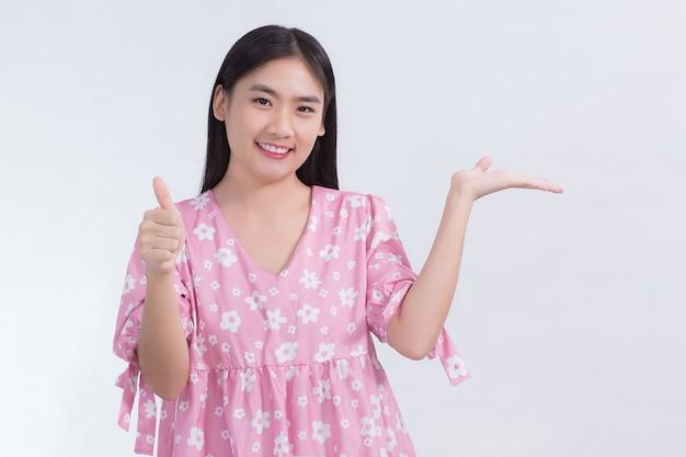 Belle femme asiatique aux cheveux longs noirs en chemise blanche montre le pouce vers le haut et présente quelque chose