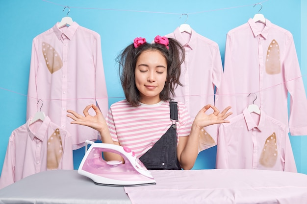 Belle femme asiatique aux cheveux noirs garde les yeux fermés médite pendant la pause après le repassage habillé avec désinvolture étant occupée mur bleu femme au foyer