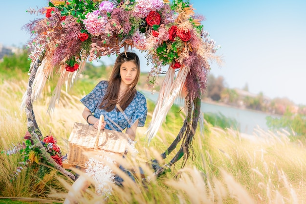 Belle femme asiatique ayant du temps détendu sur une balançoire