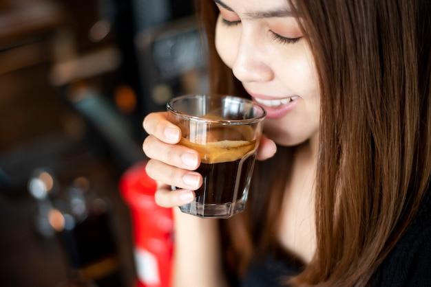 Belle femme asiatique boit du café