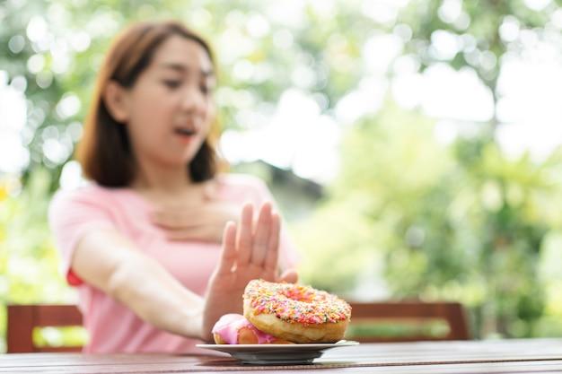 Belle femme asiatique en bonne santé assis sur la terrasse, refusant de manger le beignet