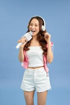 Belle femme asiatique chantant un karaoké isolé sur fond bleu.