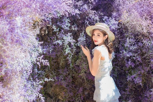 Une belle femme asiatique avec un chapeau crème se dresse parmi un beau jardin de fleurs violettes en arrière-plan.