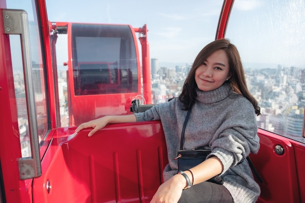 Une belle femme asiatique chevauchant une grande roue rouge au japon