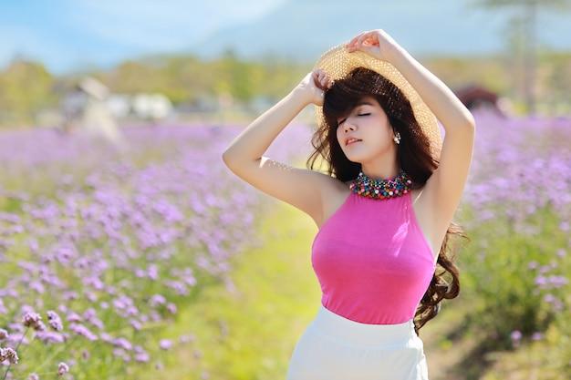 Belle femme asiatique, cheveux longs en robe mignonne sur verveine déposée en hiver avec un ciel bleu.