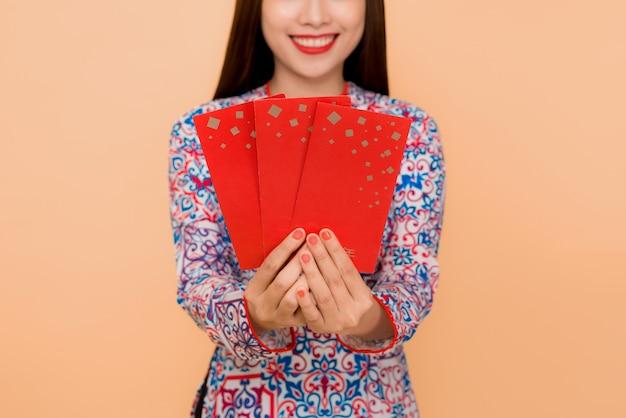 Belle femme asiatique en costume de festival traditionnel ao dai tenant de l'argent de poche chanceux