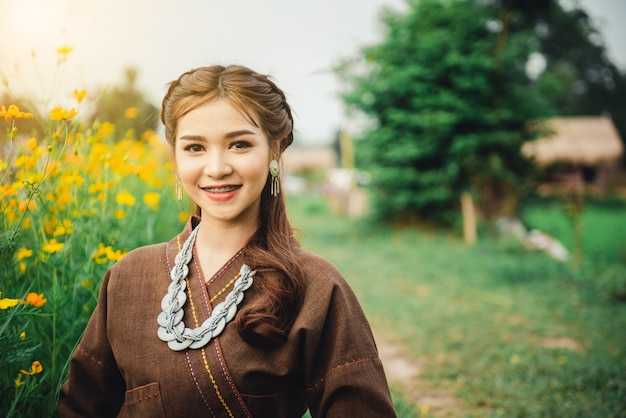 Belle femme asiatique en costume local assis sur le sol et profiter de naturel dans un champ de riz