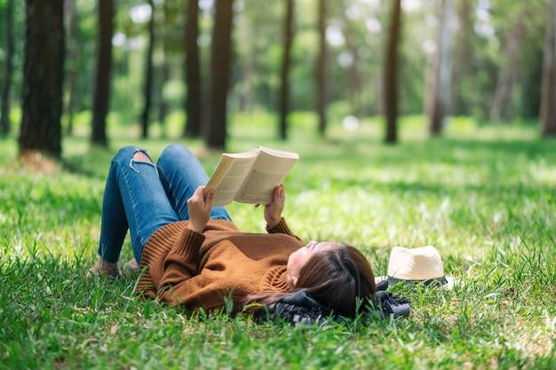 Une belle femme asiatique couchée et lisant un livre dans le parc