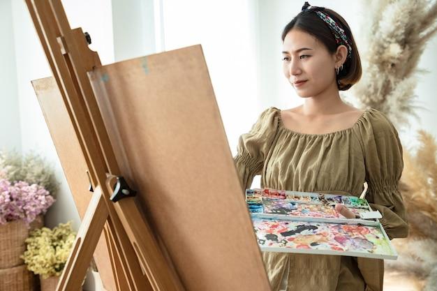 Belle femme asiatique dans un champ d'été avec pinceau à dessin et peintures colorées sur des planches de papier en studio.