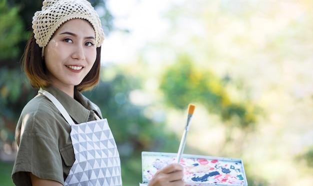 Belle femme asiatique dans un champ d'été avec pinceau à dessin et peintures colorées sur des planches de travail en papier dans le jardin.