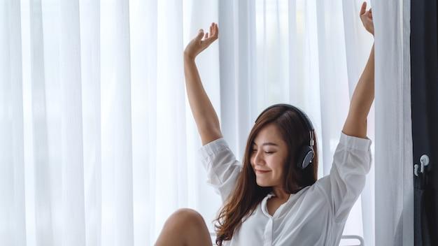 Une belle femme asiatique dansant tout en écoutant de la musique avec un casque dans la chambre, des concepts de bonheur et de relaxation