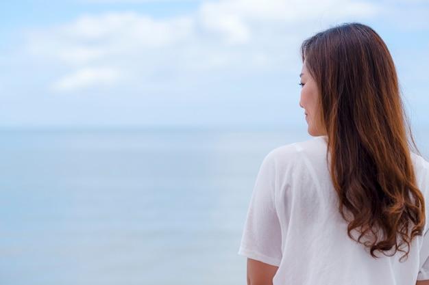 Une belle femme asiatique debout au bord de la mer