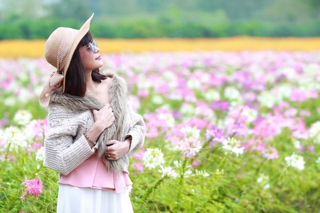 Belle femme asiatique debout dans la nature parmi les champs de fleurs cosmos avec pacifique