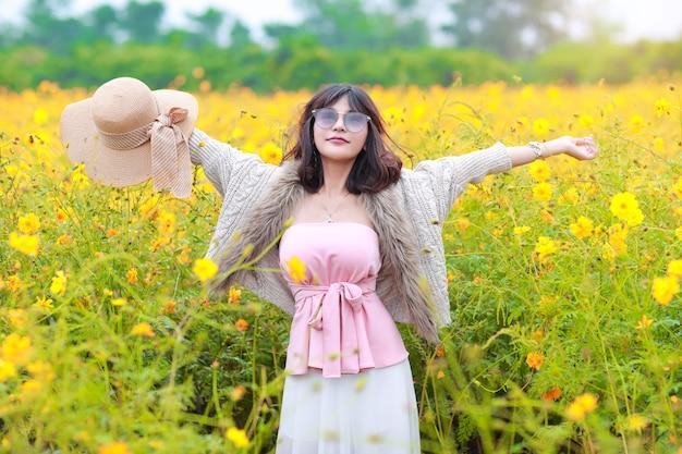Belle femme asiatique debout dans la nature parmi les champs de fleurs cosmos tout en levant les mains avec paisible et souriant