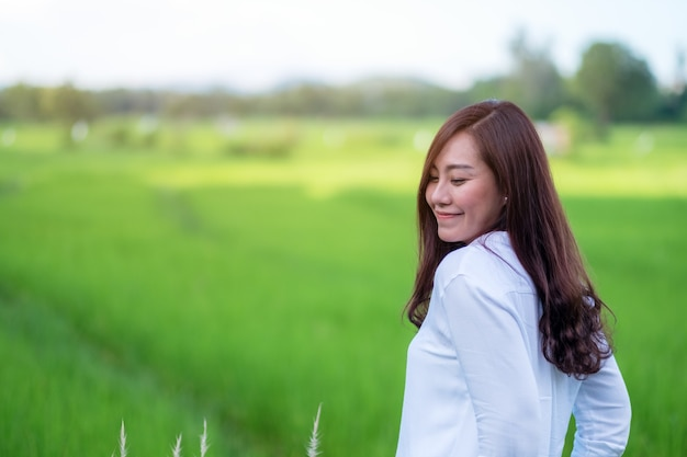 Une belle femme asiatique debout devant une rizière verte avec un sentiment détendue et heureuse
