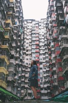 Une belle femme asiatique debout parmi le bâtiment résidentiel bondé de la communauté à quarry bay, hong kong