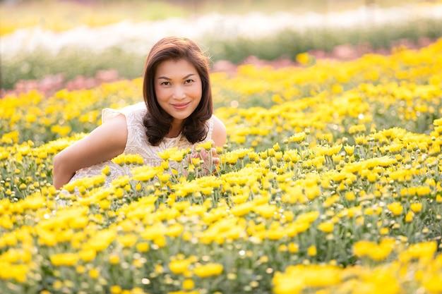 Belle femme asiatique debout et souriante dans un jardin de fleurs tropicales avec bonheur avec la chaleur du soleil de l'arrière-plan.