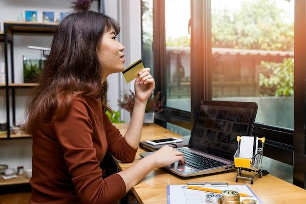 Belle femme asiatique détenant une carte de crédit et utilisant un ordinateur portable.