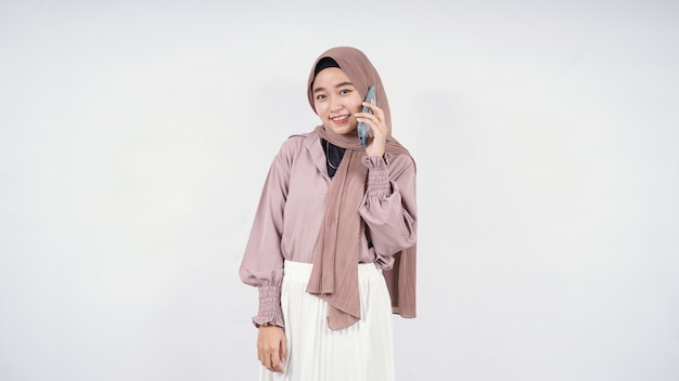 Belle femme asiatique écoutant quelque chose au téléphone et se sentant heureuse isolée sur fond blanc