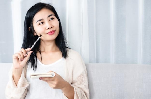 Belle femme asiatique écrivant la planification pour faire la liste sur le bloc-notes