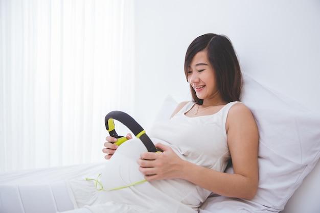 Belle femme asiatique enceinte à l'aide d'écouteurs sur sa bosse de bébé