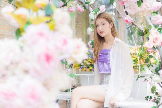 Une belle femme asiatique est assise sur une chaise blanche dans le jardin fleuri rose rose au premier plan