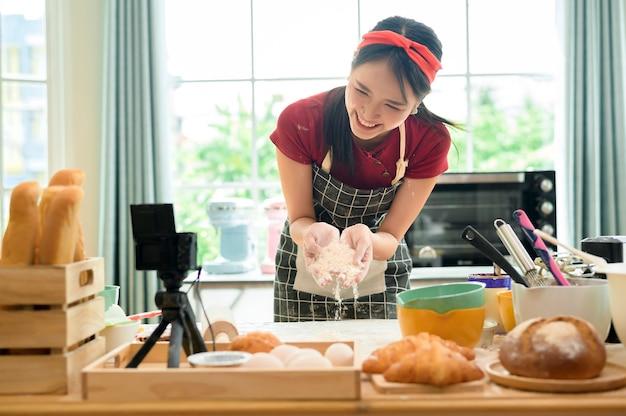 Une belle femme asiatique fait de la boulangerie, diffuse en direct ou enregistre une vidéo sur les réseaux sociaux dans sa maison