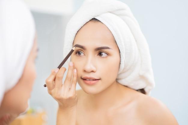 Belle femme asiatique fait maquillage crayon à sourcils