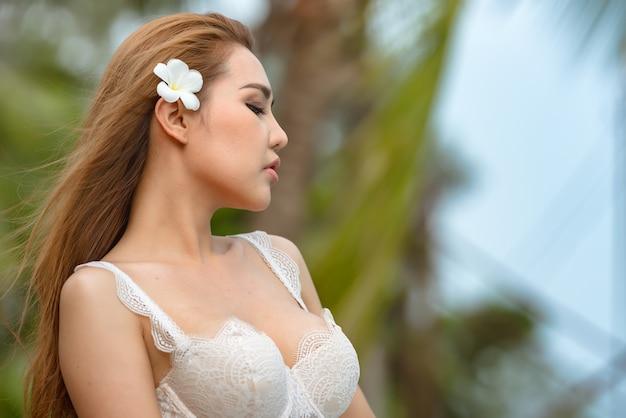 Belle femme asiatique ou femme thaïlandaise, elle porte une robe blanche