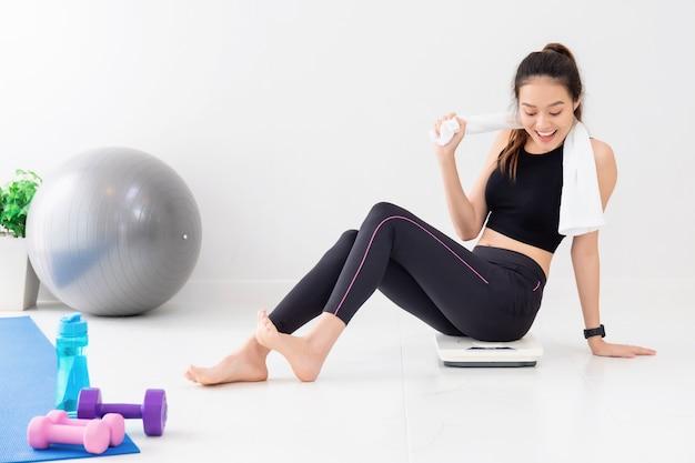 Belle femme asiatique heureuse se reposant après l'exercice et assise sur l'échelle de poids à l'arrière-plan de la salle de gym à domicile. exercice pour perdre du poids, augmenter la flexibilité et resserrer la forme.
