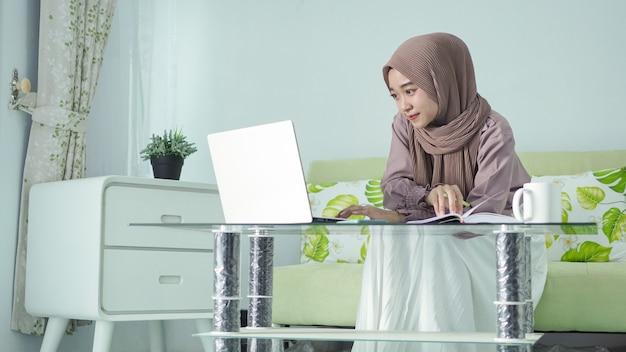 Belle femme asiatique en hijab travaillant à domicile en regardant l'écran pour prendre des notes dans son livre