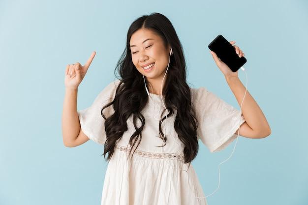 Belle femme asiatique isolée sur mur bleu à l'aide de musique d'écoute de téléphone mobile