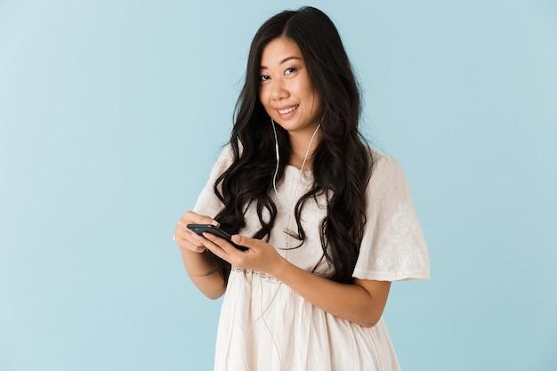 Belle femme asiatique isolée sur mur bleu à l'aide de téléphone mobile