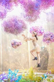 Une belle femme asiatique en jolie robe sourit tout en tenant un bouquet de fleurs dans ses mains