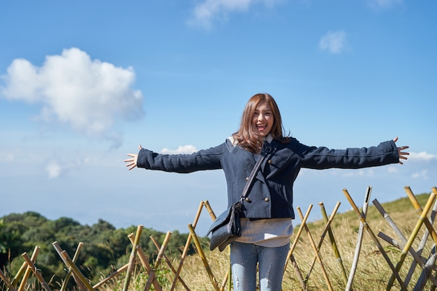Belle femme asiatique lève la main et profiter de la vue au sommet de la montagne et du ciel bleu