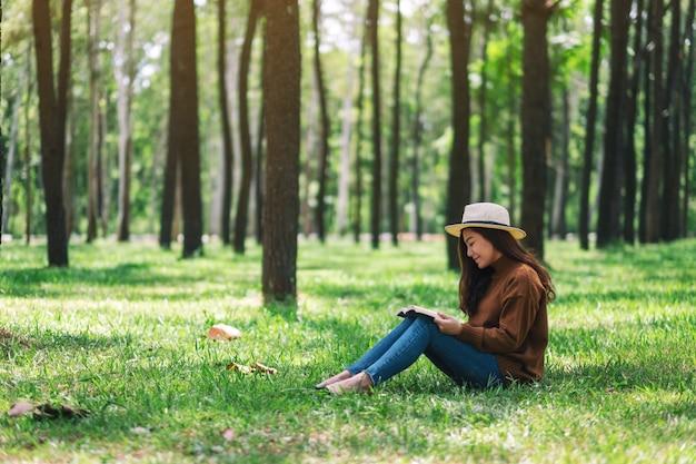 Une belle femme asiatique lisant un livre assis dans le parc