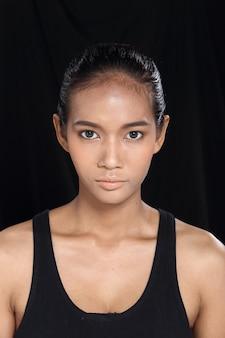 Belle femme asiatique longue et droite de peau bronzée de cheveux noirs en robe noire mince, maquillage de mode, éclairage de studio fond de tissu sombre espace de copie isolé