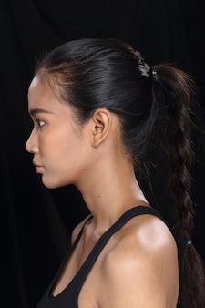 Belle femme asiatique longue peau bronzée cheveux noirs en robe noire mince, maquillage de mode, éclairage de studio fond de tissu sombre espace de copie isolé, vue arrière arrière