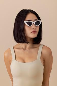 Belle femme asiatique avec des lunettes de soleil posant