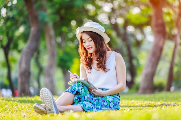 Belle femme asiatique mains avec un stylo écrit un cahier et elle était assise sur l'herbe à l'extérieur