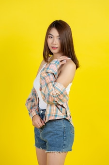 Belle femme asiatique sur mur jaune