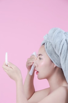 Belle femme asiatique nettoie le visage sur un fond rose.