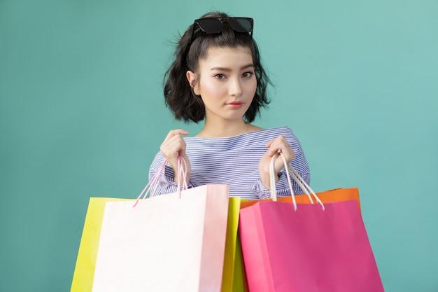 Belle femme asiatique avec de nombreux sacs à provisions