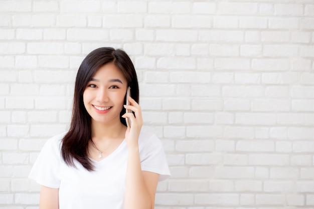 Belle femme asiatique parle téléphone intelligent