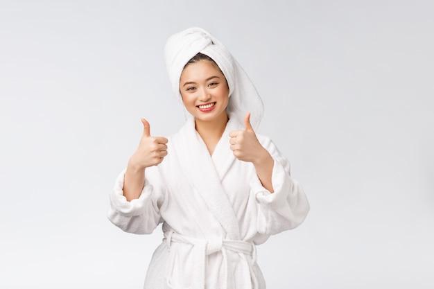 Belle femme asiatique peau parfaite montrant les pouces vers le haut isolé