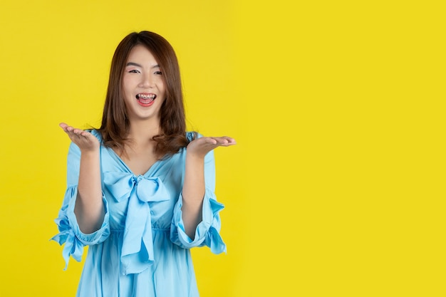 Belle femme asiatique pointant la main vers un espace vide de côté sur le mur jaune