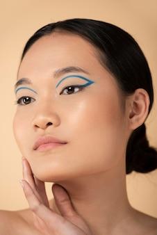 Belle femme asiatique portant un eye-liner bleu