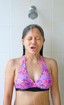 Belle femme asiatique portant un maillot de bain sous la douche.
