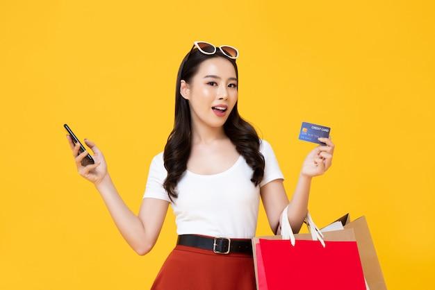Belle femme asiatique portant des sacs à provisions montrant la carte de crédit à la main